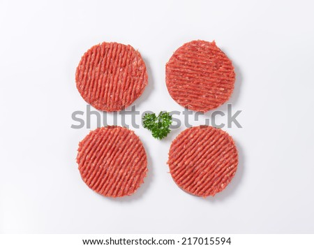 four raw hamburger patties with parsley on white background - stock photo