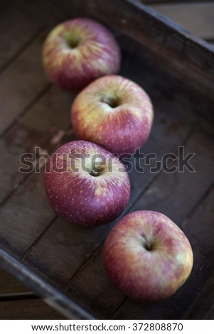 four red apples in a wooden basket - stock photo