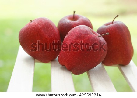 Four red apples with blurred green background.