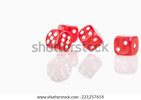 Four red bouncing dice isolated on white background with reflection - stock photo