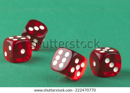 Four red bouncing dice On green background with some shadow