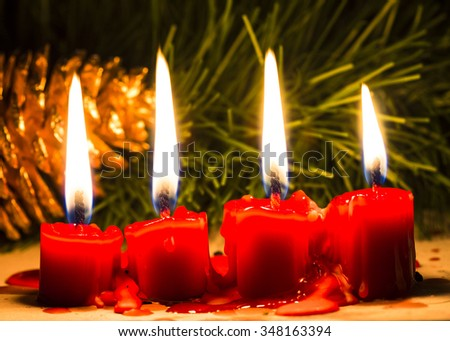 Four Red candle  against Christmas tree and decorated on the table, in the night time - stock photo