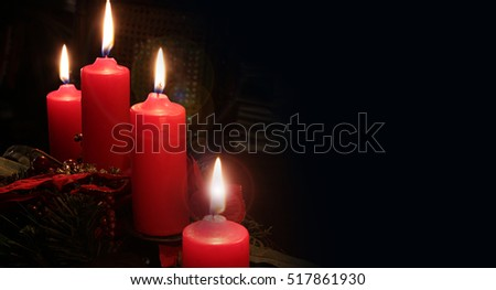Four red candles with Christmas decorations illuminating the darkness