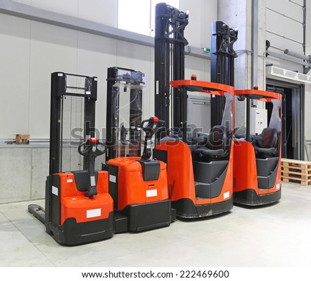 Four red forklift trucks in distribution warehouse - stock photo