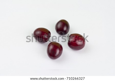 Four red fresh cherries on white background