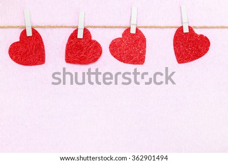 Four red hearts hang on white clothespins. Postcard for Valentines day - stock photo