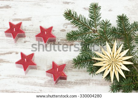 Four red starry advent candles with fir branch on wooden background
