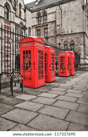 four red telephone boxes on the street of London