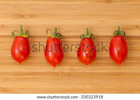 Four red tomatoes on wooden surface