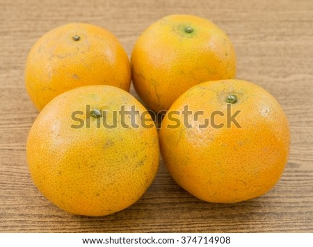 Four Ripe and Sweet Oranges on A Wooden Table, Orange Is The Fruit of The Citrus Species. - stock photo