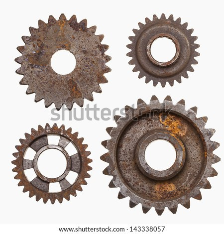 Four rusty gears isolated on a white background.