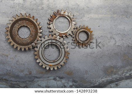 Four rusty metal gears sit on a grungy steel background. - stock photo