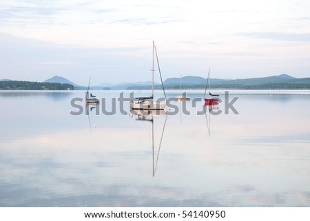 Four sailboats reflecting in calm water.