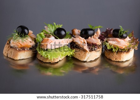 Four sandwiches with grilled salmon, cream cheese, lettuce and black olives on a dark grey background. - stock photo