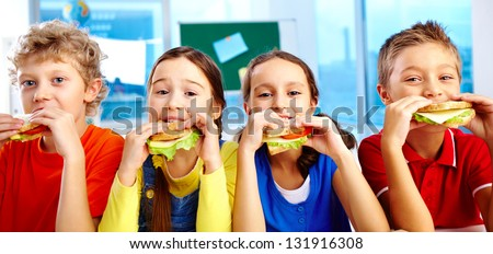 Four schoolkids looking at camera while having lunch during break - stock photo