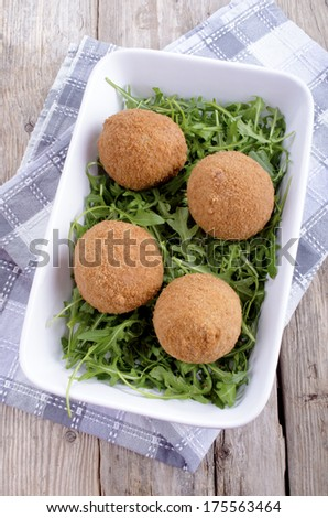 four scotch eggs and wild rocket in a white bowl - stock photo