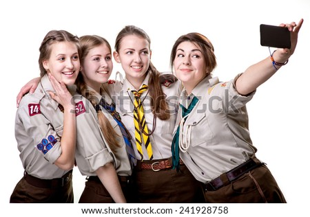 Four scout girls making selfie photo with mobile phone isolated on white background - stock photo