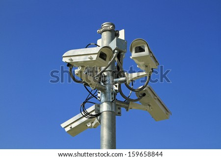 Four security cameras against blue sky background