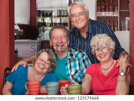 Four senior citizens laughing together in cafe - stock photo
