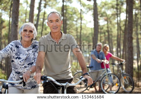 four senior people doing bike in a pine forest