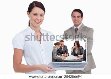 Four serious engineers looking at plans sitting at a table against smiling saleswoman presenting laptop screen with colleague behind her - stock photo