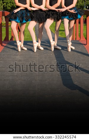 Four sets of ballerina legs in pointe shoes outdoors in a park setting. Room for copy.