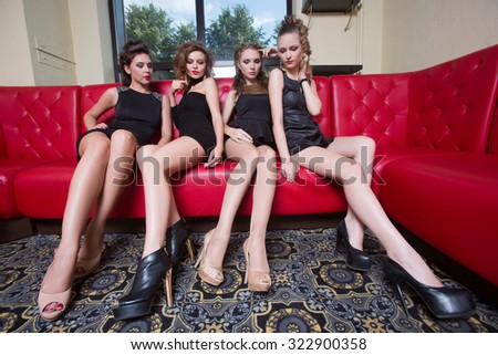 Four sexy girls on a red couch. in the interior - stock photo