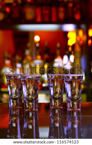 four shots tequila with lime and salt on wooden table bar, background bright lights