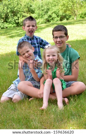 four siblings joking around during a photo shoot - stock photo
