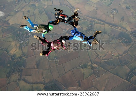 Four skydivers doing formations - stock photo