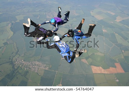 Four skydivers in freefall doing formations - stock photo