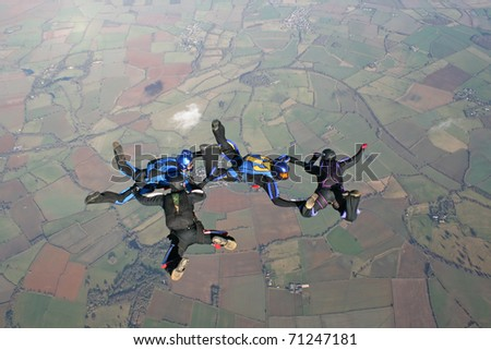 Four skydivers practicing their formations - stock photo
