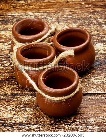 Four Small Empty Handmade Pottery Pots with Rope closeup on Textured Wooden background