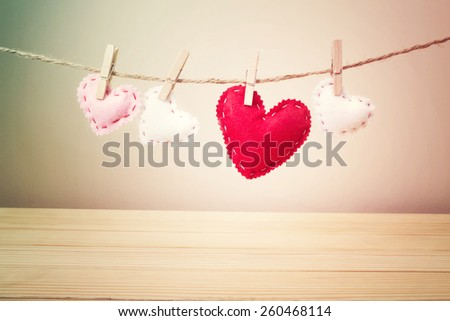 Four Small White, Pink and Red Hearts with Stitches Hanging on a String with Clothespin above the Wooden Table on Light Brown Background - stock photo