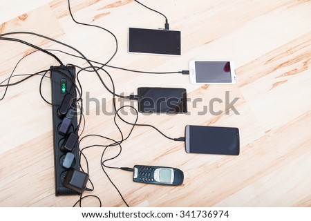 four smartphones and one classic phone connected to chargers - stock photo