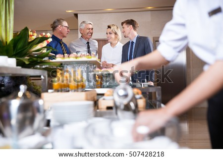 Four Smiling Business People at Buffet Table