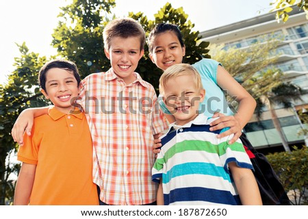 Four smiling children looking at the camera - stock photo