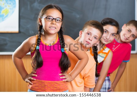 Four smiling schoolchildren standing in classroom against blackboard - stock photo