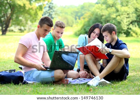 four smiling student studying in green park  - stock photo
