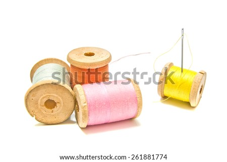 four spools of thread with needle on white background - stock photo