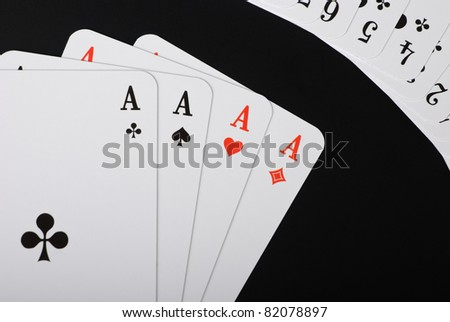 Four spread aces and additional playing cards in the right corner on black background - stock photo