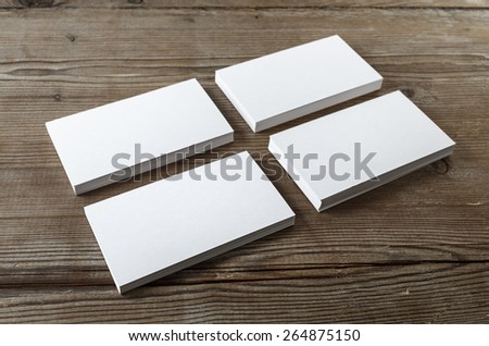 Four stacks of blank business cards on a dark wooden background. Mockup for branding identity. Shallow depth of field. - stock photo
