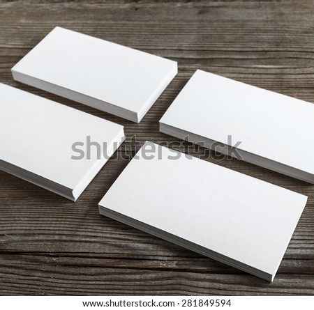 Four stacks of blank business cards on a dark wooden background. Mockup for branding identity. Shallow depth of field. Selective focus. - stock photo
