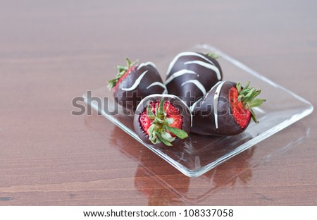 four strawberries covered in dark chocolate served on a clear plate - stock photo