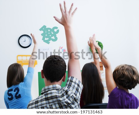 Four students eagerly raise their hands in an attempt to be the first to answer.
