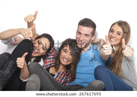 Four students hold up their hands with thumbs up