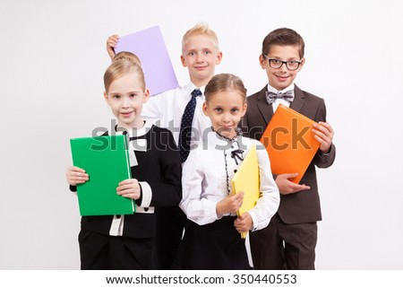 Four students smiling on a white background with books in their hands.