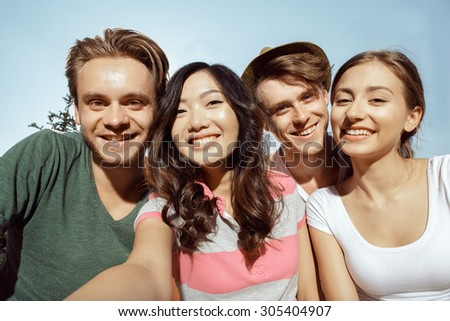 Four students smiling warmly into the camera