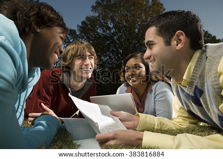 Four students studying outdoors - stock photo