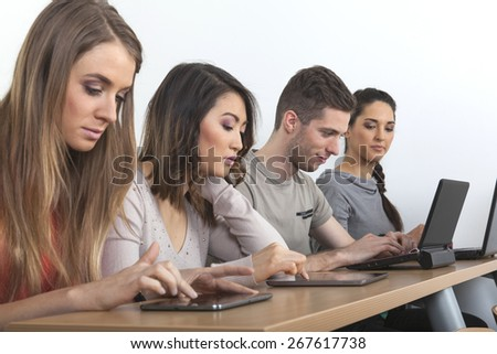 Four students with laptops and tablet sit in a row